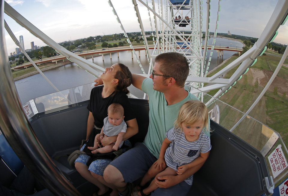Photo -  Seth and Tarah Stallings, of Pink, ride the Wheeler Ferris wheel on Thursday with their children, Nova, 4 months, and Ruby , 2 1/2. [Photo by Bryan Terry, The Oklahoman]