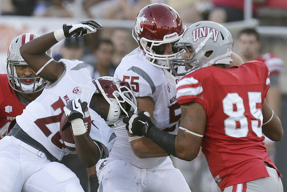 Photo -   UNLV defensive lineman Jordan Sparkman (85) grabs the face mask of Washington State running back Leon Brooks (23) while being blocked by offensive linesman Wade Jacobson (55) in the first quarter during an NCAA college football game, Friday, Sept. 14, 2012, in Las Vegas. (AP Photo/Julie Jacobson)