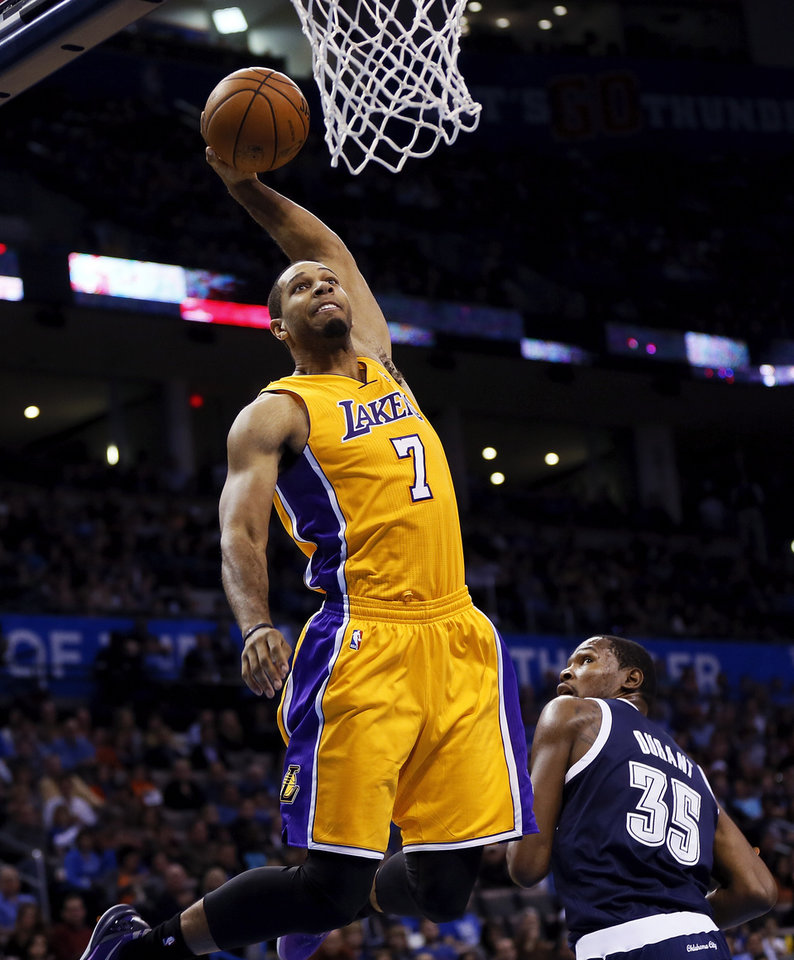 Photo - LA's Xavier Henry (7) dunks near Oklahoma City's Kevin Durant (35) during an NBA basketball game between the Los Angeles Lakers and the Oklahoma City Thunder at Chesapeake Energy Arena in Oklahoma City, Friday, Dec. 13, 2013. OKC won, 122-97. Photo by Nate Billings, The Oklahoman
