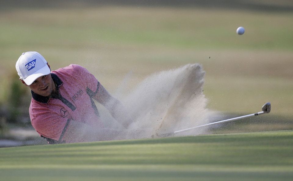 Photo - Martin Kaymer, of Germany, hits out of the bunker on the 10th hole during the third round of the U.S. Open golf tournament in Pinehurst, N.C., Saturday, June 14, 2014. (AP Photo/Eric Gay)