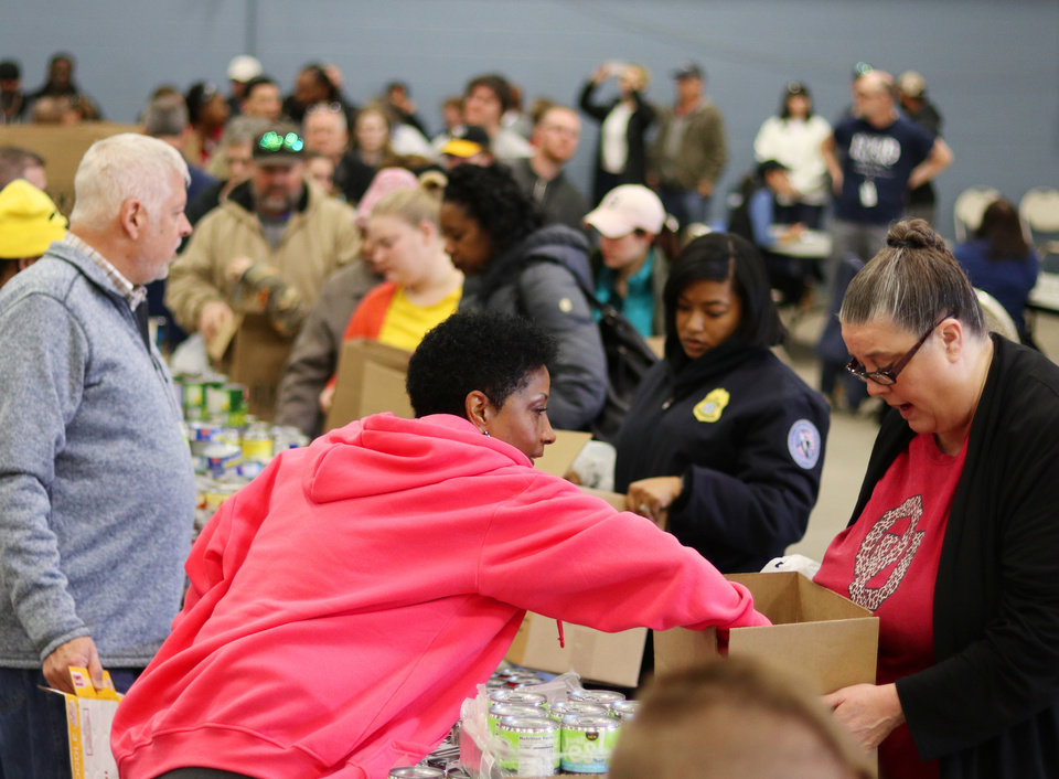 Photo - Volunteer from American Airlines,Patricia Driver, left, places food in a box for Kim Sites, who works at FAA, during a free food distribution for federal employees by the Regional Food Bank of Oklahoma at State Fair Park Monday, January 21, 2019.  Photo by Doug Hoke, The Oklahoman