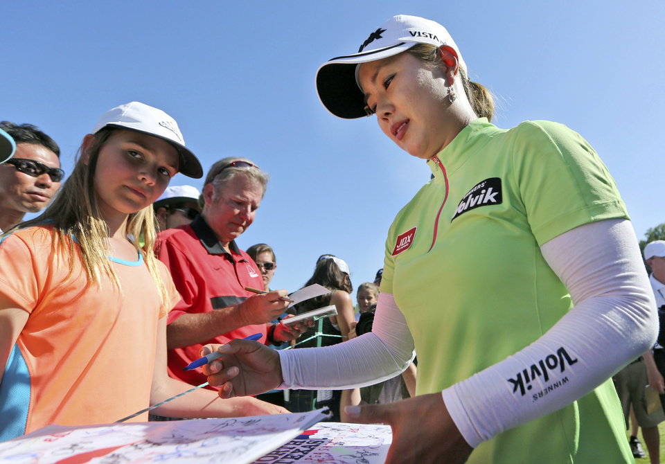 Photo - Meena Lee, of South Korea, signs autographs after her third round in the North Texas LPGA Shootout golf tournament at the Las Colinas Country Club in Irving, Texas, Saturday, May 3, 2014. (AP Photo/LM Otero)