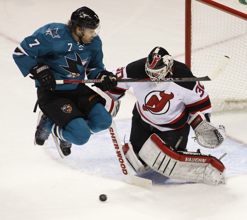 San Jose Sharks\' Brad Stuart, left, jumps up in front of New Jersey Devils goalie Martin Brodeur during the first period of an NHL hockey game on Saturday, Nov. 23, 2013, in San Jose, Calif. (AP Photo/George Nikitin)
