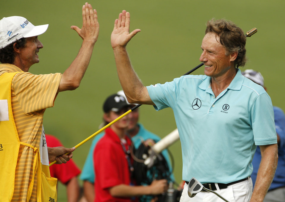 Photo - Bernhard Langer of Munich, Germany, right, celebrates with his caddie Terry Holt after winning the  Senior Players Championship golf tournament at Fox Chapel Golf Club in Pittsburgh, Sunday, June 29, 2014. Langer defeated Jeff Sluman in the second hole of a playoff to win the tournament. (AP Photo/Gene J. Puskar)