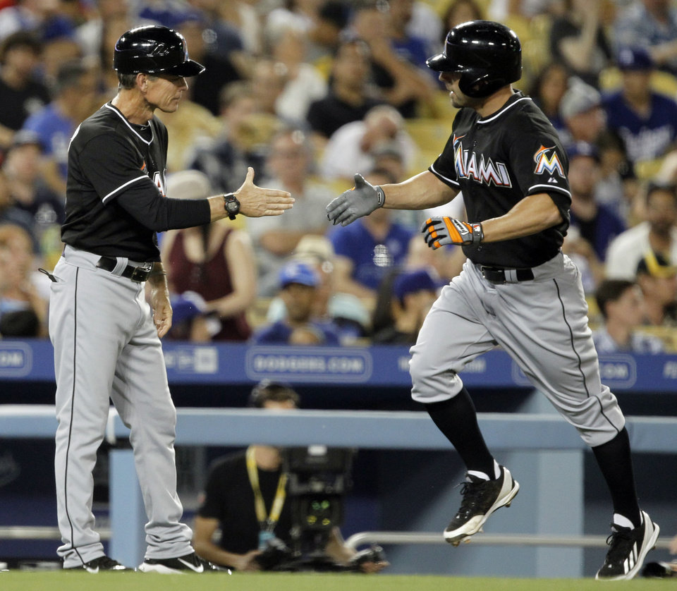 Photo - Miami Marlins third base coach Brett Butler, left, congratulates Reed Johnson on his two-run home run against the Los Angeles Dodgers in the fourth inning of a baseball game Wednesday, May 14, 2014, in Los Angeles. (AP Photo/Alex Gallardo)