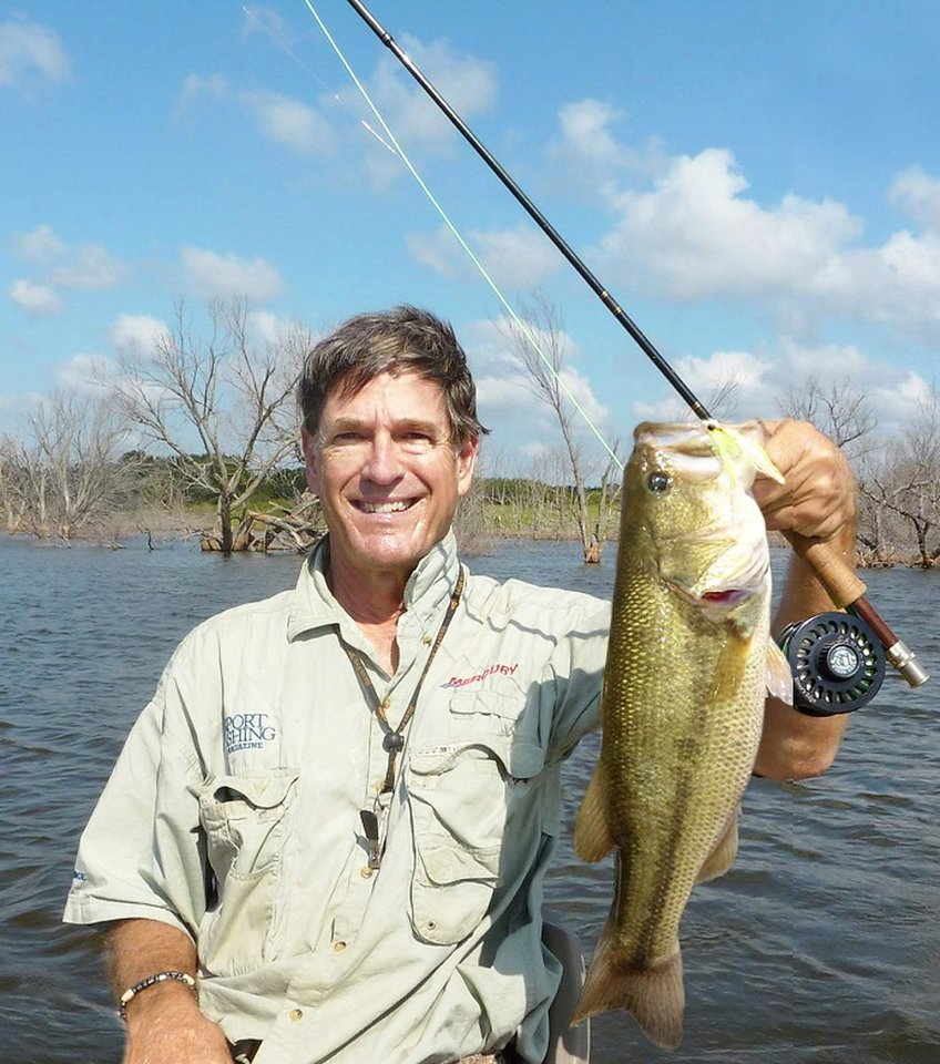 Photo - The author, Hal McKnight of Oklahoma City, holds a 7-pound bass caught on a fly rod. Photo Provided