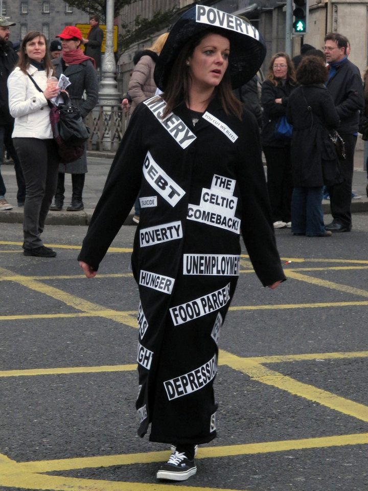 Photo -   Dublin school assistant Lizzy Stringer,26, parades in a costume depicting Ireland's economic woes during an anti-austerity protest Saturday, Nov. 24, 2012. The government says it will unveil Ireland's sixth straight austerity budget next month in hopes of reducing the country's 2013 deficit to 8.6 percent, still nearly triple the spending limit that eurozone members are supposed to observe. (AP Photo/Shawn Pogatchnik)
