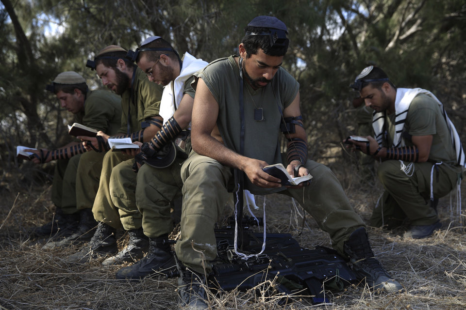 Photo - Israeli reserve soldiers pray after returning to Israel from the Gaza Strip near the Israel Gaza border, Monday, Aug. 4, 2014. A brief cease-fire declared by Israel and troop withdrawals slowed violence in the Gaza war Monday, but an attack on an Israeli bus that killed one person in Jerusalem underscored the tensions still simmering in the region as Israeli airstrikes resumed late in the day. (AP Photo/Tsafrir Abayov)
