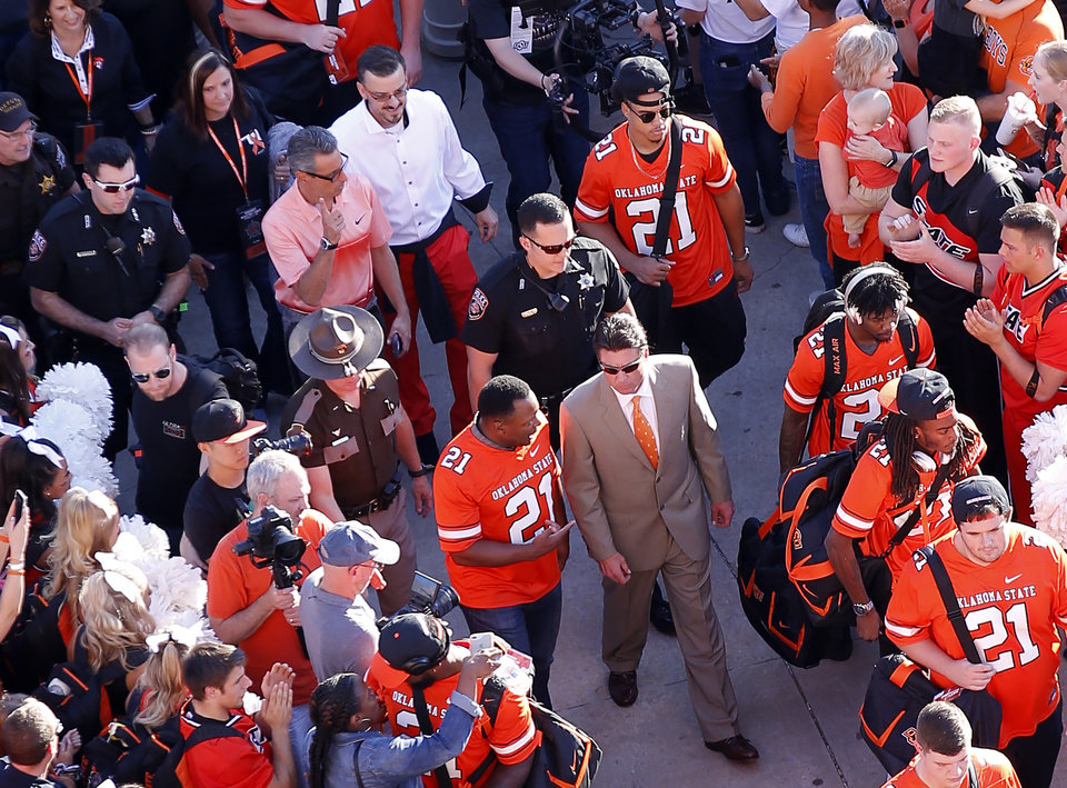 Photo - Oklahoma State head coach Mike Gundy and Barry Sanders walk into the stadium the walk  during a college football game between Oklahoma State (OSU) and University of Texas a at Boone Pickens Stadium in Stillwater, Okla., Saturday, Oct. 27, 2018. Photo by Sarah Phipps, The Oklahoman