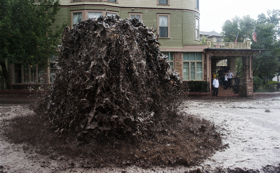 Photo - Flood water shoots out of a sewer on Canon Avenue next to the Cliff House in Manitou Springs, Colo. Thursday, Sept. 12, 2013 as storms continue to dump rain over the Waldo Canyon burn scar. (AP Photo/The Gazette, Michael Ciaglo)