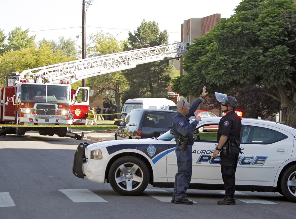 Photo - Police block the road in front of  an apartment where the suspect in a theatre shooting lived in Aurora, Colo., on Friday, July 20, 2012. As many as 12 people were killed and 50 injured at a shooting at the Century 16 movie theatre on Friday. The suspect is identified as 24-year-old James Holmes.  (AP Photo/Ed Andrieski) ORG XMIT: COEA119