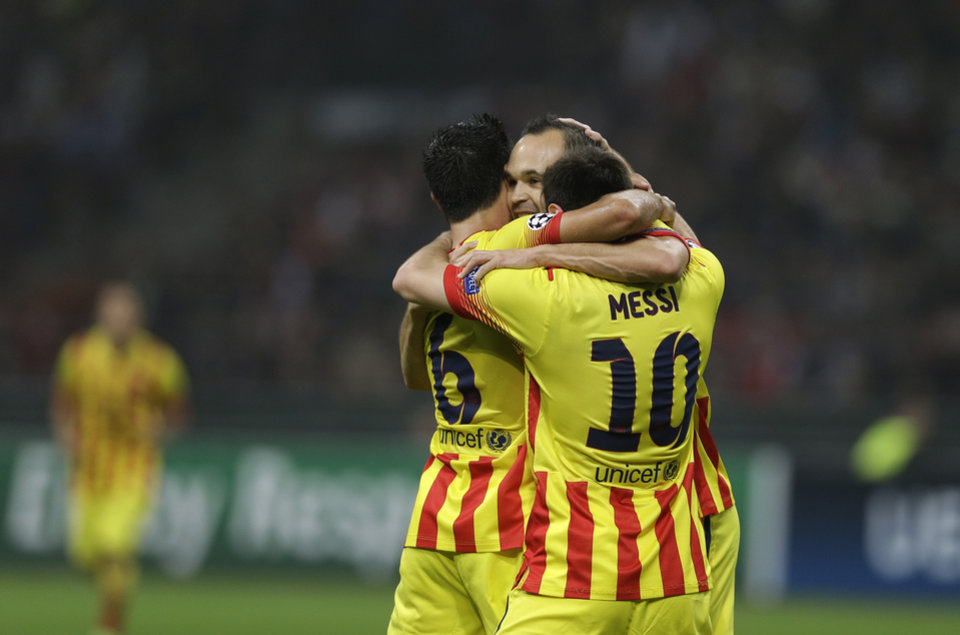 Photo - Barcelona's Lionel Messi celebrates with teammates Xavi Hernandez and Andres Iniesta after scoring a goal during a Champions League, Group H, soccer match between AC Milan and Barcelona at the San Siro stadium, in Milan, Italy, Tuesday, Oct. 22, 2013.  (AP Photo/Luca Bruno)
