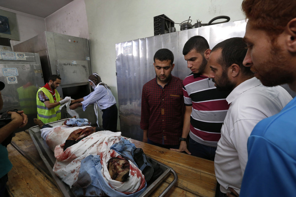 Photo - EDS NOTE: GRAPHIC CONTENT -In this Friday, July 18, 2014 photo, Palestinians gather around the body of Ahmed Barnasawi, 22, at the Shifa hospital's morgue as workers prepare him for burial, in Gaza City, Friday, July 18, 2014. Barnasawi was killed during an overnight Israeli strike. Israeli troops pushed deeper into Gaza on Friday to destroy rocket launching sites and tunnels, firing volleys of tank shells and clashing with Palestinian fighters in a high-stakes ground offensive meant to weaken the enclave's Hamas rulers. (AP Photo/Lefteris Pitarakis)