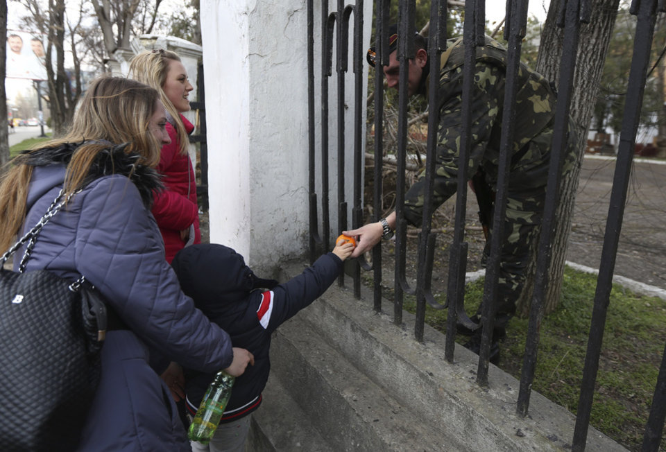 Photo - A child gives fruit to a Ukrainian officer at the Ukrainian Military Prosecutor's Office in Simferopol, Crimea, Thursday, March 20, 2014. The lower house of Russian parliament voted Thursday to make Crimea a part of Russia following Sunday's Crimean referendum in which its residents overwhelmingly backed breaking off from Ukraine and joining Russia. (AP Photo/Maxin Vetrov)