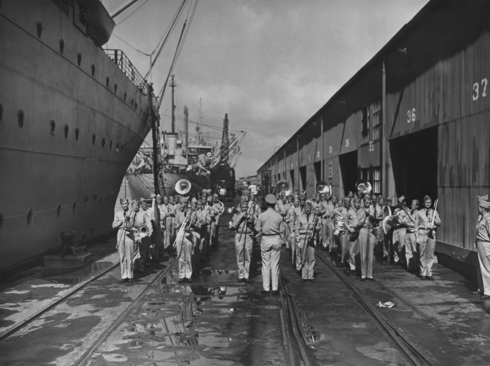 """Photo - Never was the 45th division band quite so popular as when it showed up on the port of embarkation dock to stage a little jam session and buck up the Thunderbirds' morale with 'Boomer Sooner' and  'Oklahoma!' """"  Photograph is U.S. Army photo.  Photographer unknown.  Original date unknown.  Entered the library 03/31/1951."""