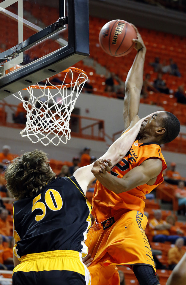 Oklahoma State's Markel Brown dunks over Alex Lundry during the college basketball game between Oklahoma State University and Ottawa(Kan.) at Gallagher-Iba Arena in Stillwater, Okla., Thursday, Nov. 1, 2012. (AP Photo/The Oklahoman, Sarah Phipps)
