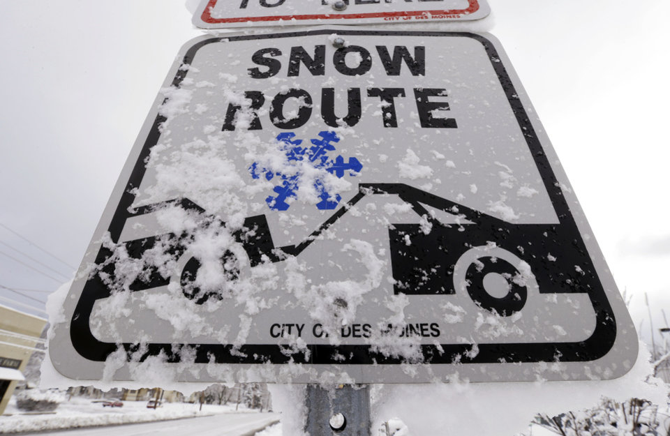 Photo - Snow clings to a Snow Route sign on a city street, Thursday, Dec. 20, 2012, in Des Moines, Iowa. The first widespread snowstorm of the season began a slow crawl across the Midwest on Thursday with some areas receiving as much as 15 inches of snow. (AP Photo/Charlie Neibergall)