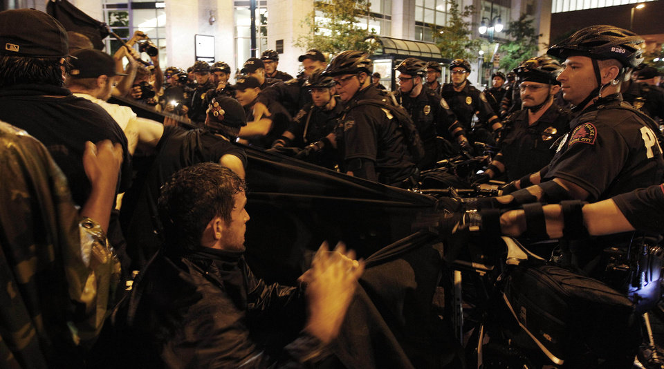 Photo - Occupy Demonstrators use a tarp to push against a police barricade during an unscheduled protest march, Tuesday, Sept. 4, 2012, in Charlotte, N.C. The Democratic National Convention begins today. (AP Photo/Chuck Burton) ORG XMIT: XDNC164