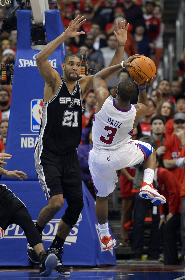 Los Angeles Clippers guard Chris Paul, right, attempts a shot in the last seconds of the game as San Antonio Spurs center Tim Duncan defends in Game 4 of an NBA basketball playoffs Western Conference semifinal, Sunday, May 20, 2012, in Los Angeles. The Spurs won 102-99. (AP Photo/Mark J. Terrill)