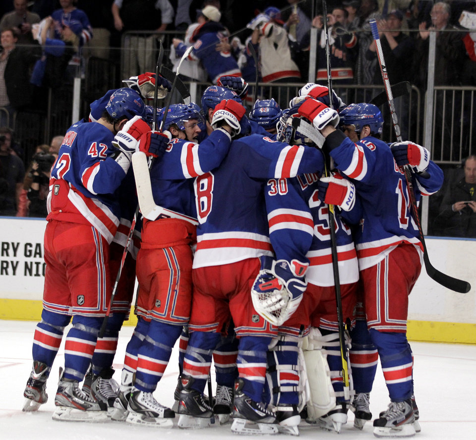 Photo -   Members of the New York Rangers celebrate after defeating the Ottawa Senators 2-1 in Game 7 of a first-round NHL hockey Stanley Cup playoff series on Thursday, April 26, 2012, in New York. (AP Photo/Julio Cortez)