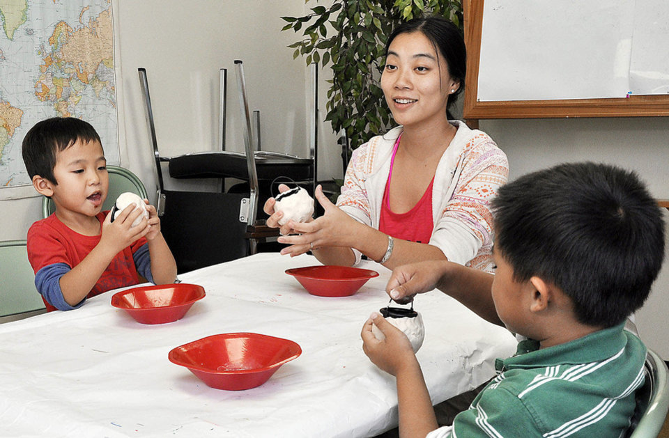 Photo - Jasmine Zhang teaches Eric Wong, left, and Ian Wu, right, the finer points of making pottery during Chinese culture classes at Trinity International Baptist Church Sunday, October 6, 2013. Photo by M. Tim Blake, for The Oklahoman