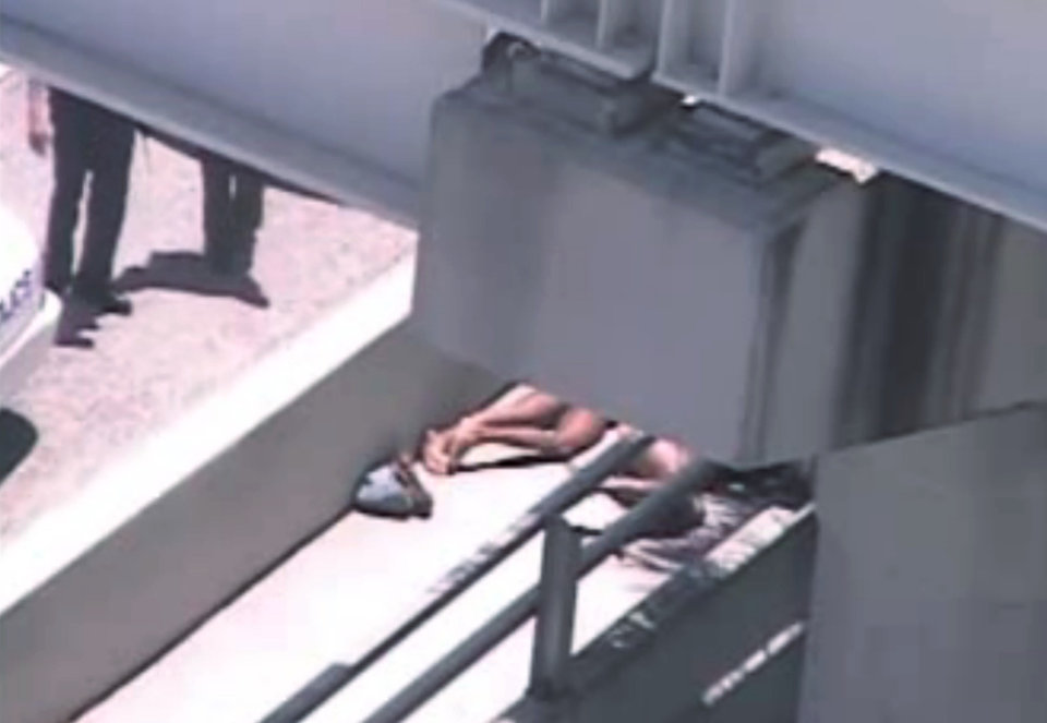 Photo -   In this image taken from video, Miami police officers stand watch near a naked man, second from right, who was shot dead by a police officer when he refused to stop chewing on the face of the naked man next to him, partially obscured by a railing, on the MacArthur Causeway ramp onto Northeast 13th Street in Miami, Saturday, May 26, 2012. The victim was taken to a nearby hospital. Police say neither man's identity is known. (AP Photo/The Miami Herald) MAGS OUT
