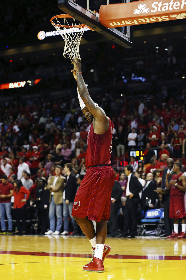 Photo - Miami Heat's LeBron James hangs onto the net during the final minute of an NBA basketball game against the Oklahoma City Thunder in Miami, Tuesday, Dec. 25, 2012. The Heat won 103-97. (AP Photo/J Pat Carter)