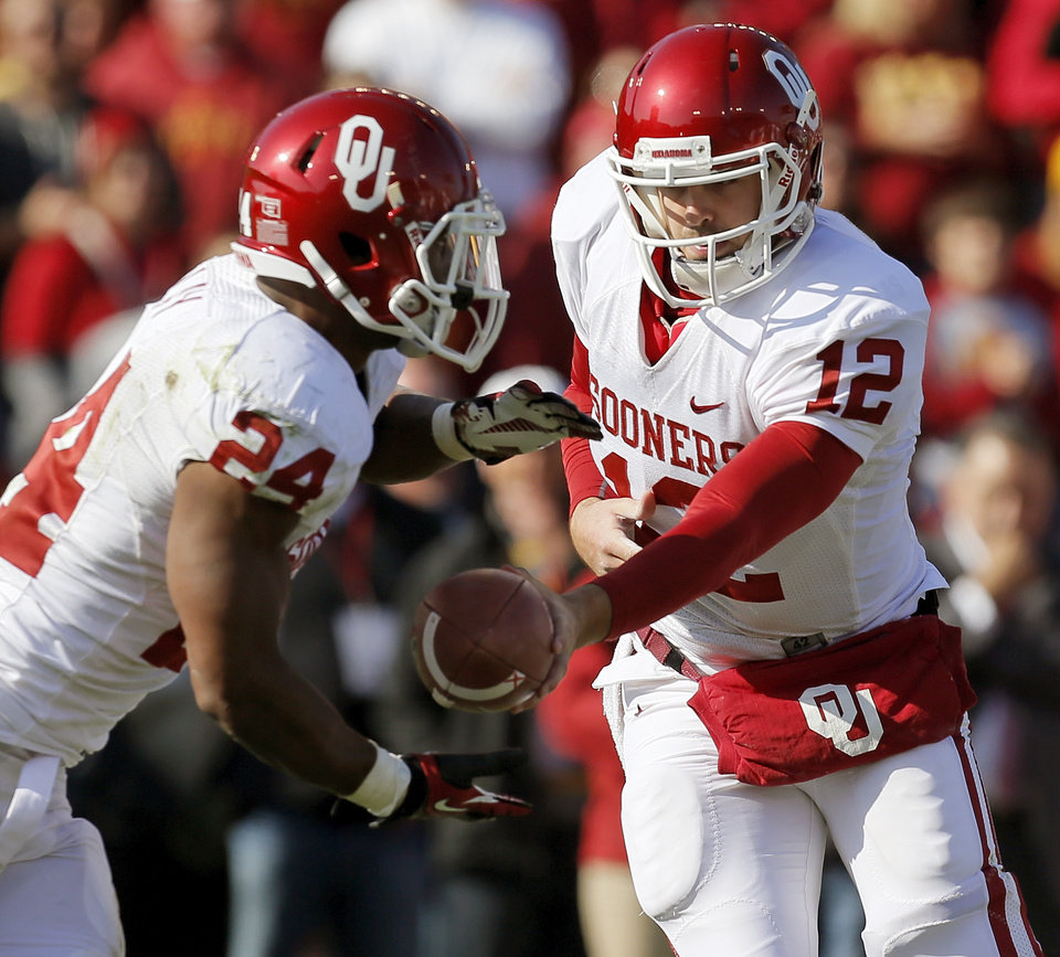 Photo - Oklahoma's Landry Jones (12) hands the ball to Brennan Clay (24) during a college football game between the University of Oklahoma (OU) and Iowa State University (ISU) at Jack Trice Stadium in Ames, Iowa, Saturday, Nov. 3, 2012. Photo by Nate Billings, The Oklahoman