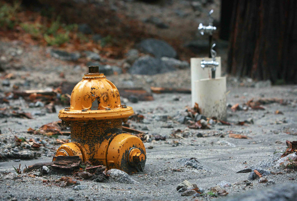 Photo - In this Sunday, Aug. 3, 2014 photo, a fire hydrant and drinking fountains are partially buried at Forest Home Christian Conference Center in Forest Falls, Calif. following a rock and mudslide. Crews on Monday have cleared several feet of mud, rocks and debris that had blocked San Bernardino County roads, stranding some 2,500 people in the rural communities of Oak Glen and Forest Falls. (AP Photo/The Press-Enterprise, David Bauman)  MAGS OUT; MANDATORY CREDIT