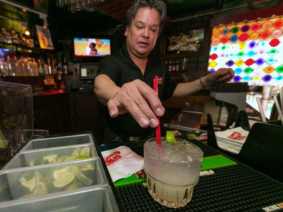 Photo - In this Monday, April 28, 2014 photo, barman Mario Sanchez mixes a margarita cocktail at the bar of El Coyote, a Mexican restaurant in Los Angeles. Thousands of restaurateurs from coast to coast who have fallen victim to the Great Green Citrus Crisis of 2014. The lime has skyrocketed in price in recent weeks, quadrupling or, in some areas, going even higher. (AP Photo)