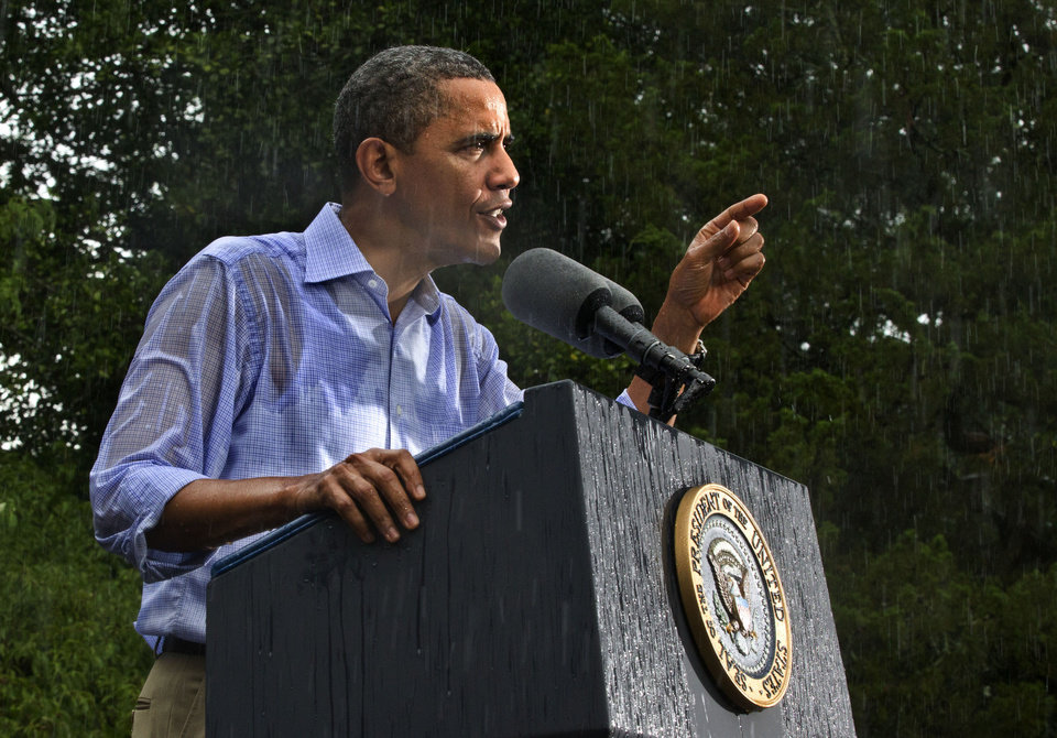Photo - FILE - In this July 14, 2012 file photo, President Barack Obama campaigns for re-election in the heavy rain at Walkerton Tavern & Gardens in Glen Allen, Va., near Richmond.  It was a year of storms, of raging winds and rising waters, but also broader turbulence that strained our moorings. Our atmosphere, our politics, our economy — rarely in memory have they seemed in such constant agitation. (AP Photo/J. Scott Applewhite, File)