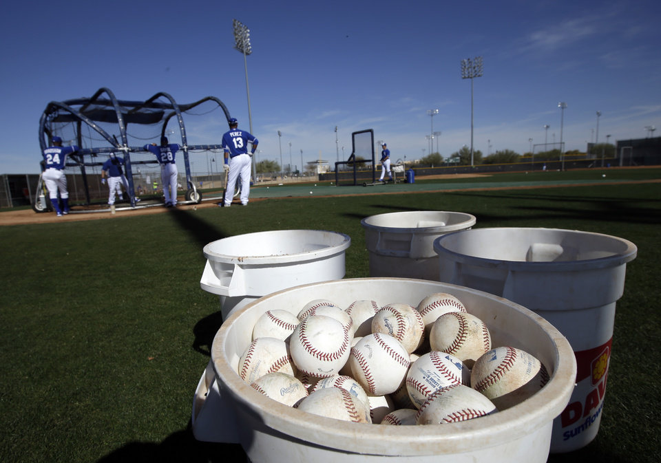 Photo - Buckets of baseballs sit on the field as Kansas City Royals catchers take batting practice during spring training baseball practice, Saturday, Feb. 15, 2014, in Surprise, Ariz. (AP Photo/Tony Gutierrez)