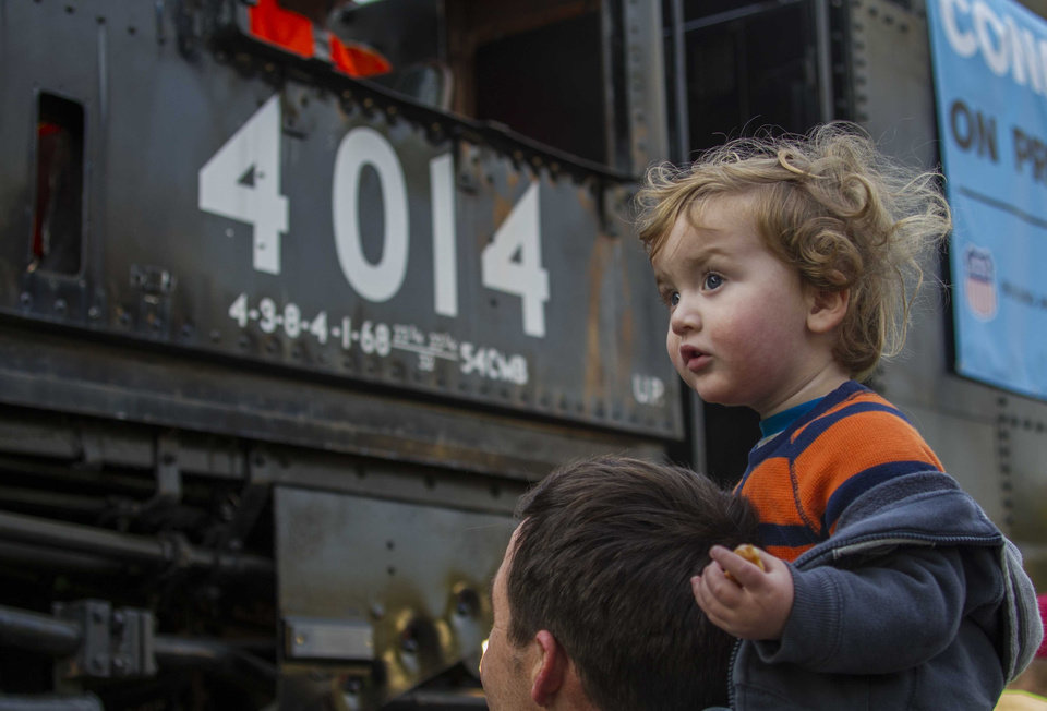 Photo - Kirk Hofstetter, of Fullerton, carries his son Theodore, 1, to view the historic locomotive, Union Pacific Big Boy No. 4014 at Metrolink Station, Sunday, Jan. 26, 2014, in Covina, Calif. (AP Photo/Ringo H.W. Chiu)