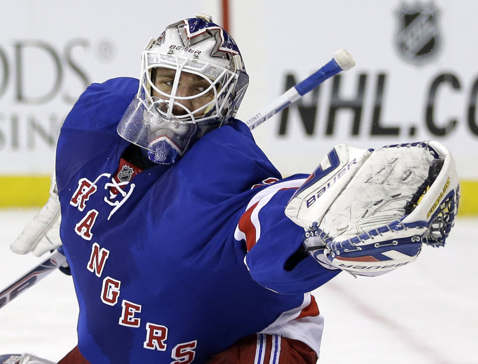 Photo - FILE - In this March 24, 2014 file photo, New York Rangers goalie Henrik Lundqvist makes a save during the first period of the NHL hockey game against the Phoenix Coyotes, in New York. Lundqvist already owns the club records for most career wins and shutouts. Both were accomplished this year in a most successful season. However, there is one key thing missing from the star goalie's resume: a Stanley Cup title. (AP Photo/Seth Wenig, File)