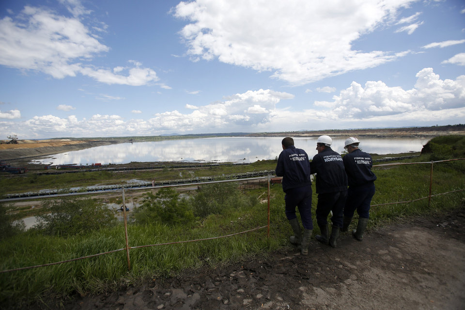 Photo - Miners look at the flooded coal pit mine near the village of Veliki Crljeni, some 30 kilometers (18 miles) south of Belgrade, Serbia, Sunday, May 18, 2014. In Serbia, more than 20,000 people have been forced from their homes. Officials there fear more flooding later Sunday as floodwaters travel down the Sava and reach the country. Serbian officials said that the flood wave might be lower than initially expected, because the river broke barriers upstream in Croatia and Bosnia. Experts said they expect Sava floodwaters to rise for two more days, then subside. (AP Photo/Darko Vojinovic)