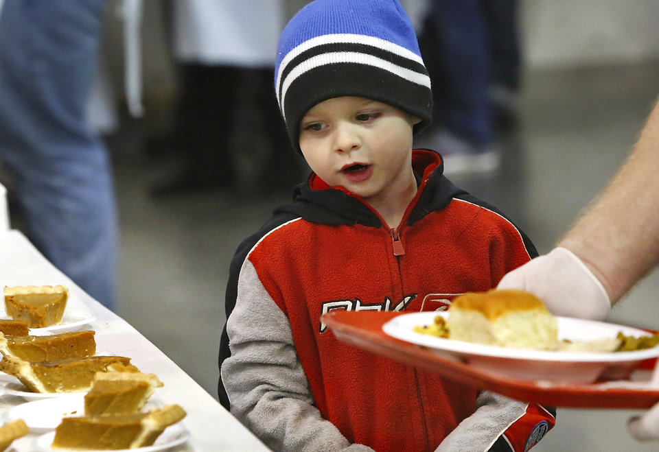 Dayton Cieszynski, 6, looks at pieces of pumpkin pie as a volunteer carries a tray carrying Dayton\'s food as the two go through the serving line. Dayton attended the event with his sister and a great aunt. Hundreds were served a traditional Christmas meal at the annual Red Andrews Dinner inside the Cox Convention Center on Christmas Day, Dec. 25, 2012. An army of volunteers showed up despite snow and ice and hazardous driving conditions. They accompanied each guest through the serving line and carried their trays and seated them at their tables. Other volunteers distributed a small mountain of toys and stuffed animals that were donated for the event. Photo by Jim Beckel, The Oklahoman