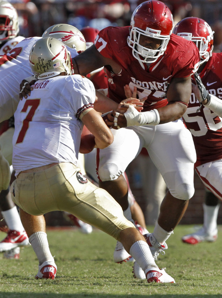 Photo - Oklahoma's Jamarkus McFarland takes down Florida State quarterback Christian Ponder (7) for a sack during the second half of the college football game between the University of Oklahoma Sooners (OU) and the Florida State University Seminoles (FSU) on Sat., Sept. 11, 2010, in Norman, Okla.  Photo by Chris Landsberger, The Oklahoman