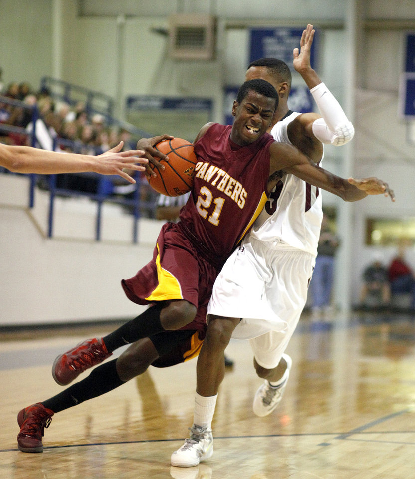 Putnam City North's Rodney Teal drives past Edmond Memorial's James Woodard during the Bruce Gray Invitational at Deer Creek High School, Saturday, Jan. 21, 2012, in Oklahoma City, Okla. Photo by Sarah Phipps, The Oklahoman