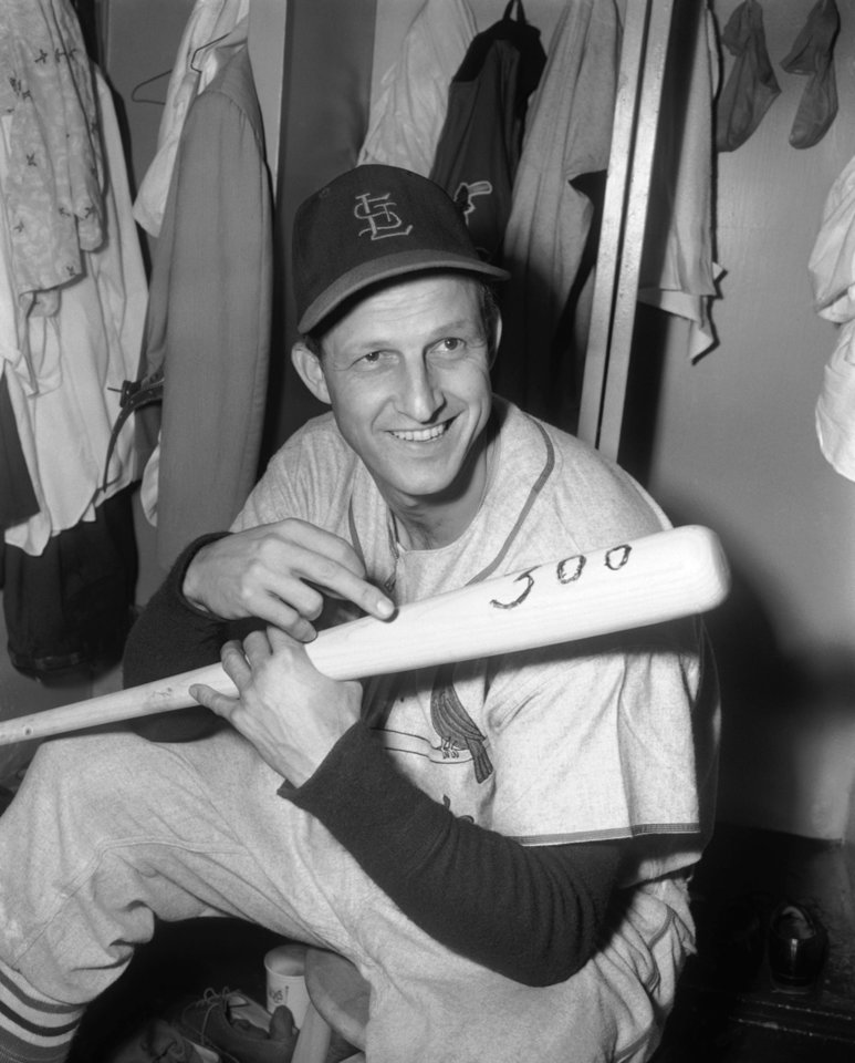 FILE - In this June 3, 1955, file photo, Stan Musial of the St. Louis Cardinals, holds bat with which he hit his 300th major league home run as he sits in clubhouse at Ebbets Field in New York, after the Cardinals 12-5 win over the Brooklyn Dodgers. Musial, one of baseball's greatest hitters and a Hall of Famer with the Cardinals for more than two decades, died Saturday, Jan 19, 2013, the team announced. He was 92. (AP Photo/Marty Lederhandler, File)