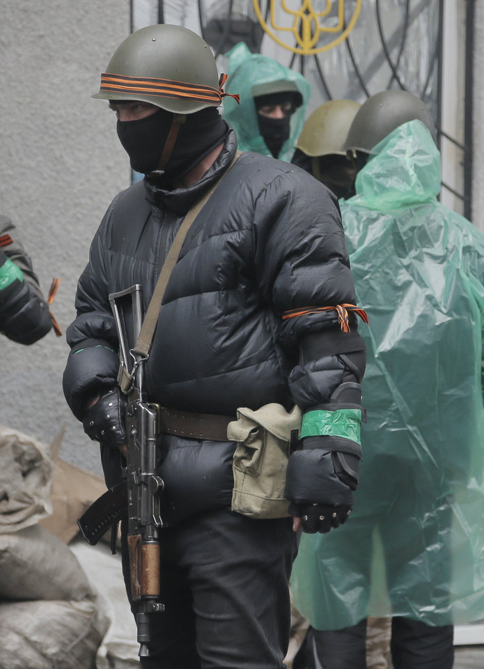Photo - A pro-Russian gunman stands guard at a seized police station in the eastern Ukrainian town of Slovyansk on Sunday, April 13, 2014. Ukrainian special forces exchanged gunfire with a pro-Russia militia in the eastern city Sunday, according to the interior minister, who said one Ukrainian security officer was killed and five others wounded. It was the first reported gunbattle in east Ukraine, where armed pro-Russia men have seized a number of law enforcement buildings in recent days. (AP Photo/Efrem Lukatsky)