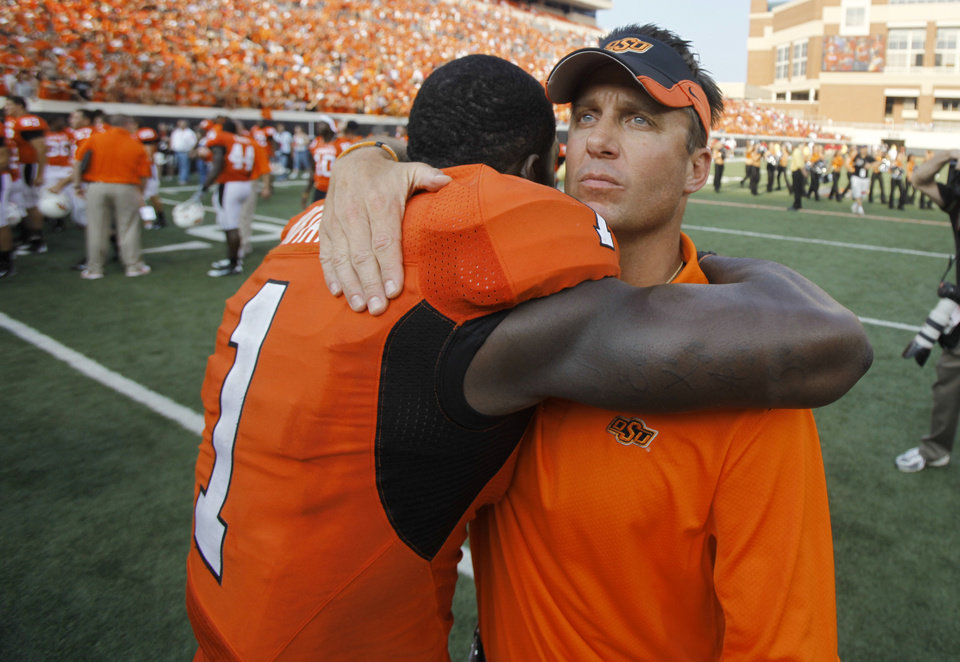 Photo - OSU head coach Mike Gundy hugs Dez Bryant after the Cowboys' 24-10 win over Georgia during the college football game between OSU and the University of Georgia at Boone Pickens Stadium on the campus of Oklahoma State University in Stillwater Saturday, Sept. 5, 2009. Photo by Chris Landsberger, The Oklahoman.