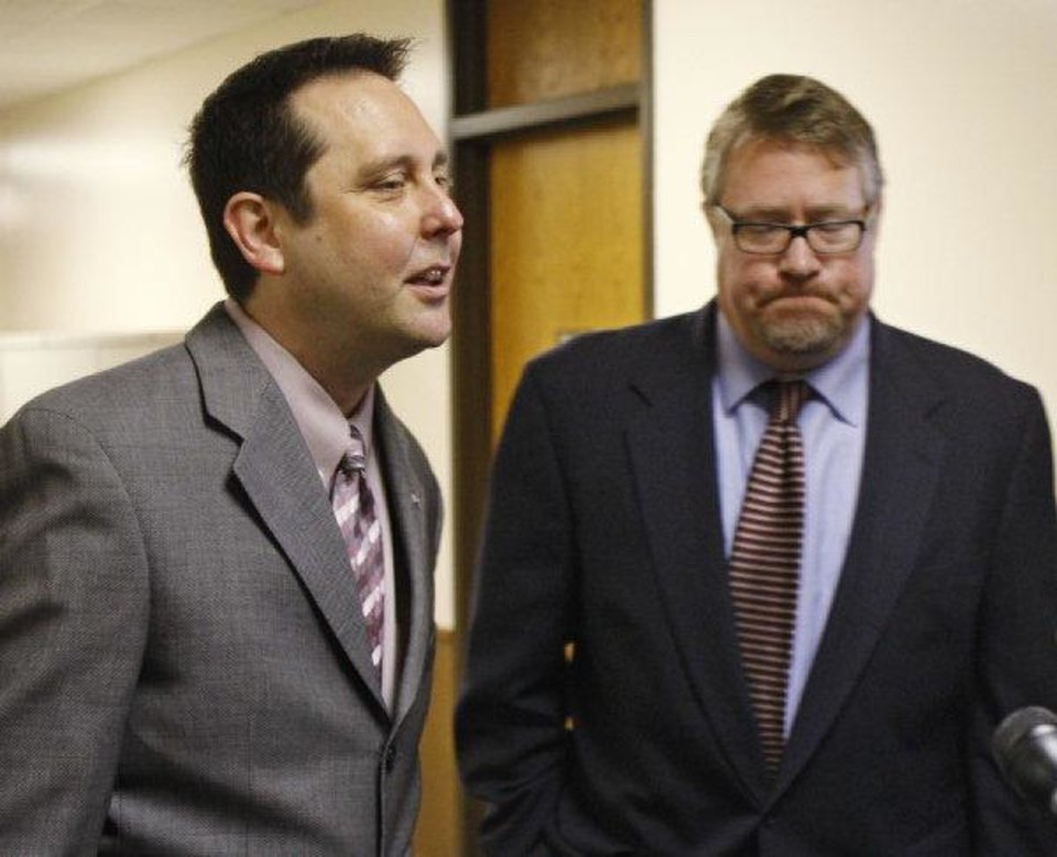 Defense attorney Matthew Haire, left, of the Oklahoma Indigent Defense System, answers a question from the media Thursday, Aug. 12, 2010, in El Reno, Okla., following a hearing in the Joshua Durcho case. At right is defense attorney G. Lynn Burch. (AP Photo/Sue Ogrocki) ORG XMIT: OKSO106