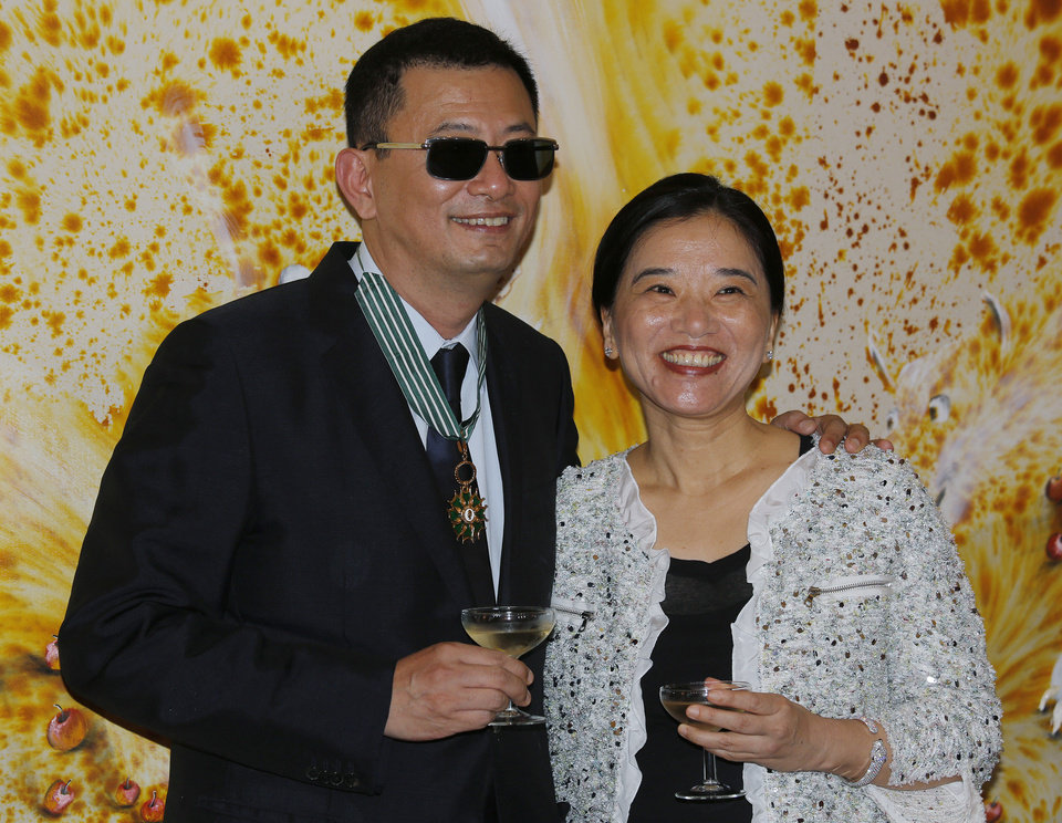 Photo - Hong Kong director Wong Kar-wai, left, and his wife Esther smile after he received the Commandeur des Arts et Lettres from French Foreign Minister Laurent Fabius, in Hong Kong Sunday, May 5, 2013. Wong has been given France's highest cultural honor. (AP Photo/Vincent Yu)