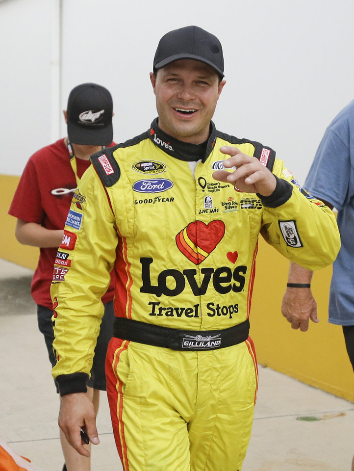 Photo - David Gilliland walks through the garage area after winning the pole position for the NASCAR Sprint Cup Series auto race at Daytona International Speedway in Daytona Beach, Fla., Friday, July 4, 2014. Qualifying was shortened due to rain. (AP Photo/John Raoux)