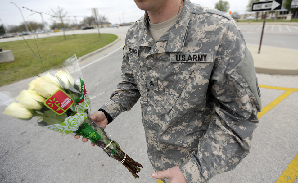 Photo - An unidentified soldier holds flowers dropped off at Fort Hood's main gate for shooting victims, Thursday, April 3, 2014, in Fort Hood, Texas. A soldier opened fire Wednesday on fellow service members at the Fort Hood military base, killing three people and wounding 16 before committing suicide. (AP Photo/Eric Gay)