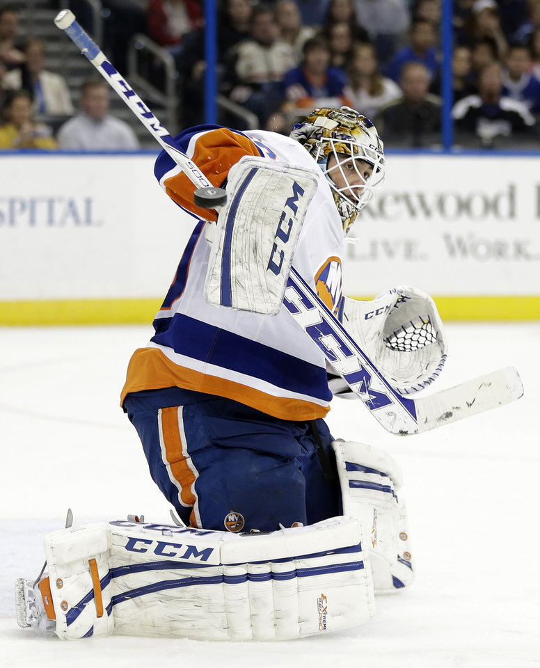 Photo - New York Islanders goalie Kevin Poulin (60) makes a blocker save on a shot by the Tampa Bay Lightning during the second period of an NHL hockey game Thursday, Jan. 16, 2014, in Tampa, Fla. (AP Photo/Chris O'Meara)