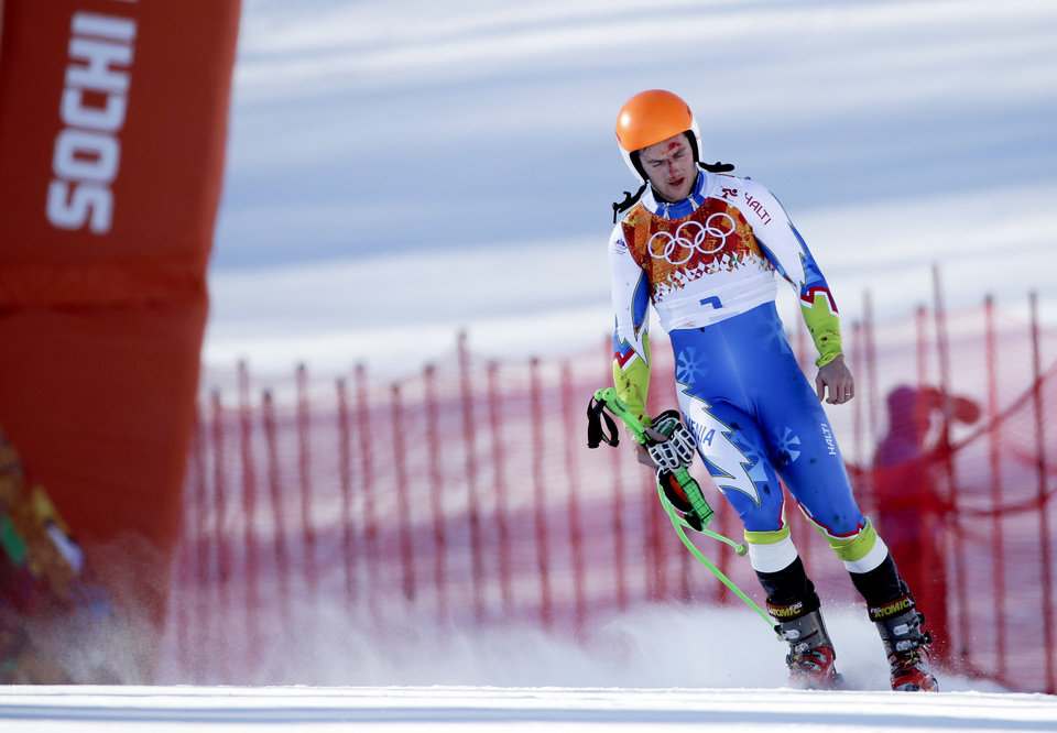 Photo - Slovenia's Rok Perko arrives in the finish area after crashing during a men's downhill training run for the Sochi 2014 Winter Olympics, Saturday, Feb. 8, 2014, in Krasnaya Polyana, Russia. (AP Photo/Gero Breloer)