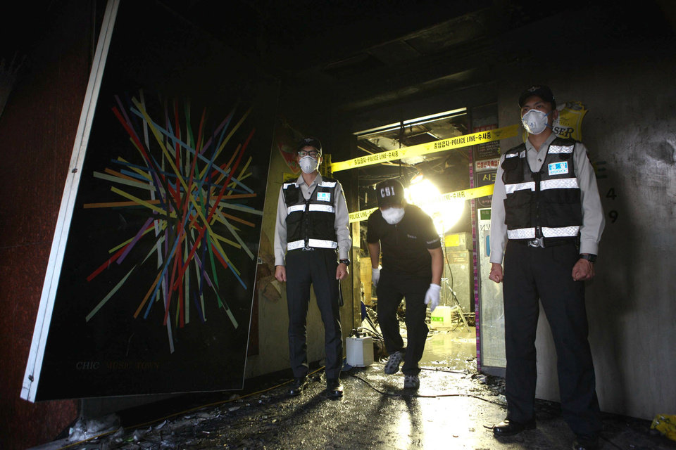 Photo -   South Korean police officers stand guard at an entrance of a karaoke bar where a fire broke out, in Busan, South Korea, Saturday, May 5, 2012. Nine people were reportedly killed in the blaze. (AP Photo/Yonhap) KOREA OUT