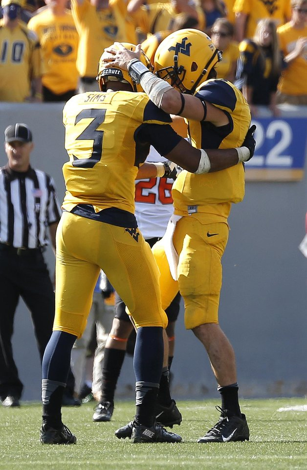 Photo - West Virginia's Clint Trickett (9) and Charles Sims (3) celebrate late in the fourth quarter of the second half of a college football game between the Oklahoma State University and West Virginia University on Mountaineer Field at Milan Puskar Stadium in Morgantown, W. Va.,   Saturday, Sept. 28, 2013. Photo by Sarah Phipps, The Oklahoman