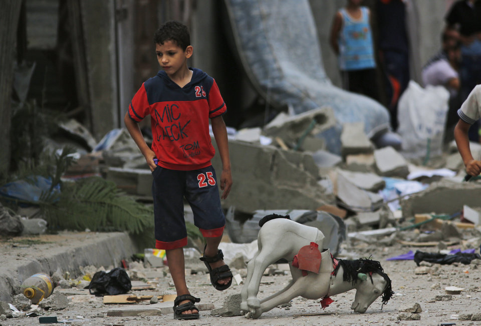 Photo - A Palestinian child walks on debris from a destroyed house, following an overnight Israeli strike in Beit Lahiya, in northern Gaza strip, Saturday, July 19, 2014. A Gaza health official says the death toll from Israel's 12-day offensive against Hamas militants has topped 300. (AP Photo/Lefteris Pitarakis)